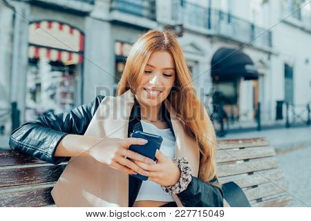 Cheerful Stylish City Girl Using Smart Phone And Sitting On Bench. Happy Business Lady Working Outdo