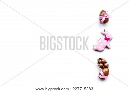 Sweets For Easter Table. Chocolate Eggs Near Cookies In Shape Of Easter Bunny On White Background To