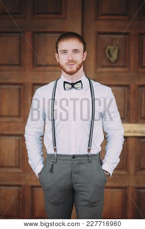 Stylish Groom In A White Shirt And Suspenders With A Red Beard