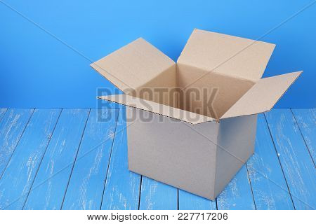 Postage And Packing Service - Open Package On A Blue Wood Background.