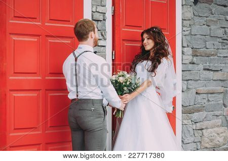 Stylish Bride And Groom Posing On The Background Of The Red Door. Weddings In Rustic Style