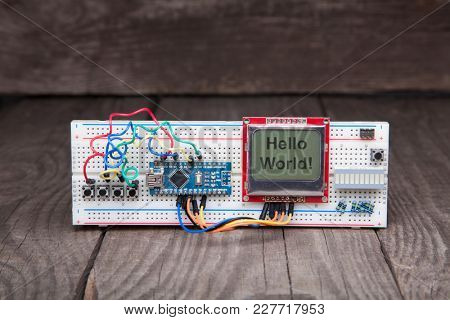 manual assembly of electronic microprocessor device. Set of spare part constructor. wood background