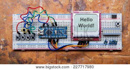 manual assembly of electronic microprocessor device. Set of spare part constructor. wood background. Helllo world.