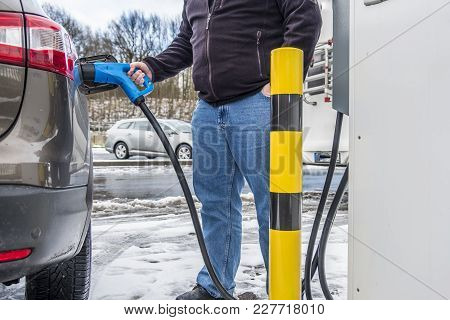 Man Charging His Electric Car In The Winter