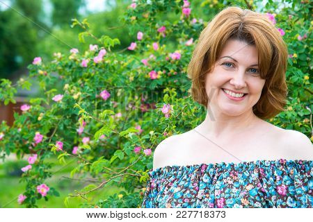 Portrait Of A Beautiful Woman On A Background Of A Blossoming Wild Rose