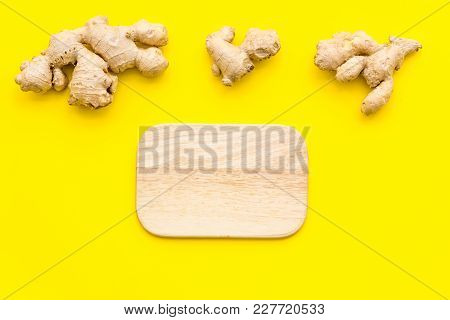 Whole And Sliced Ginger Roots, Cutting Board On Yellow Background Top View.