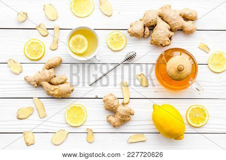 Tea For Cure Colds. Cup, Teapot, Ginger Root And Lemon On White Wooden Background Top View.