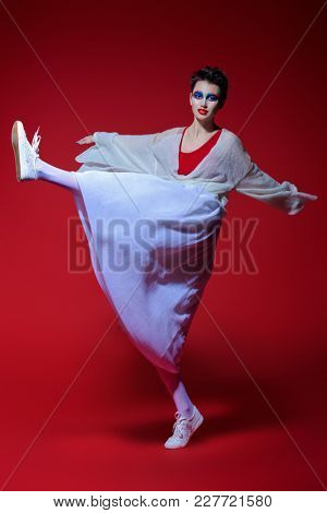 Beautiful female model in stylish clothes jumping over red background. Beauty, fashion. Studio shot.