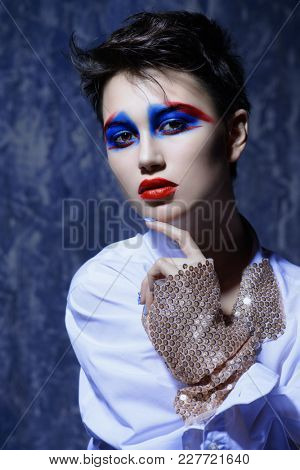 Fashion and make-up concept. Close-up portrait of an attractive young woman with creative makeup and body painting.