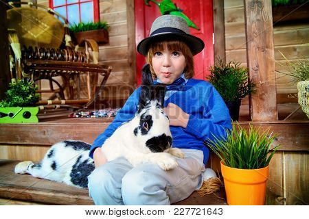 Happy little boy with bunny sitting on the porch near the wooden house. Easter holiday. Rural style, easter decoration.