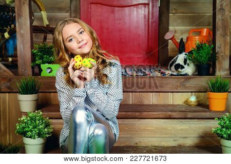 Easter holidays. Happy child girl with painted eggs is sitting on the porch near the wooden house.