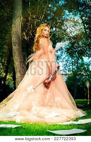 Beautiful fairy girl with the violin and sheets music on a sunny glade in the park. Musical concept. Classical music, violin.