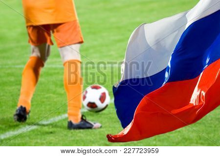 Blurred background of soccer game, Russian flag in the focus
