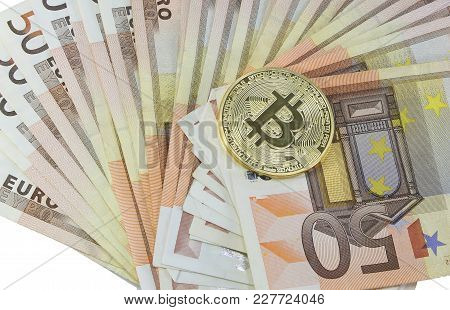 Big Golden Bitcoin Coin Over Many Euro Banknotes