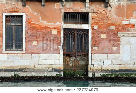Old Door In The Canal In Venice Italy During The Low Tide