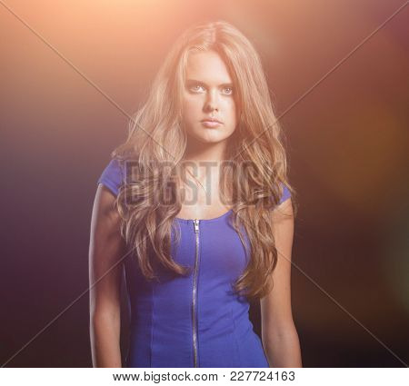 Beautiful woman in a blue dress posing on a black background