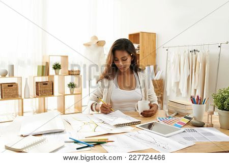 Female Fashion Designer Working On Sketches For Collection In His Studio