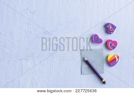 Different  Eraser In The Shape Of A Heart With A Pencil And With A Blank Little Note Paper On Blue B