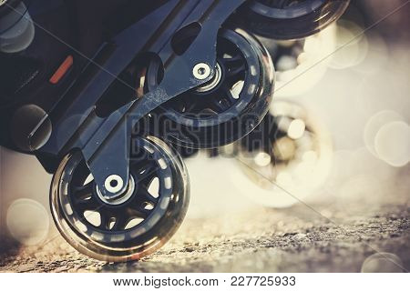 Background With The Wheels Of Roller Skates Closeup In The Rays Of The Sun.