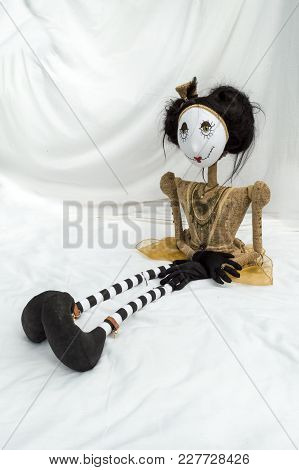 Creepy Steampunk Rag Doll Sitting With Legs Outstretched. Looking Left. Lifesize Doll On A Grungy Wh