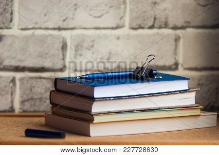 The Pen Rests On A Stack Of Diaries, An Iron Clip