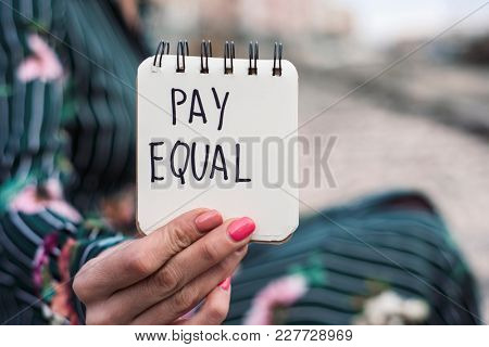 closeup of a young caucasian woman outdoors showing a notepad with the text pay equal written in it