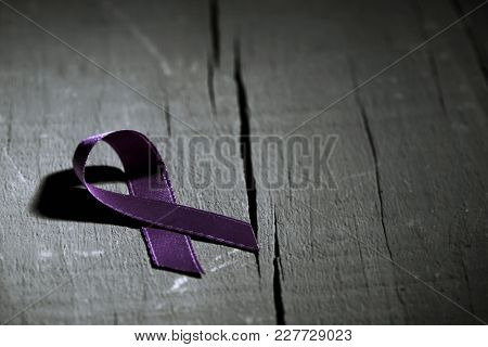 a purple ribbon for the awareness about the unacceptability of the violence against women, on a dark gray rustic wooden surface