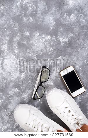 Flat Lay Of White Sneakers On Stone Background With Phone And Headphones. Teenager Casual, Love Musi