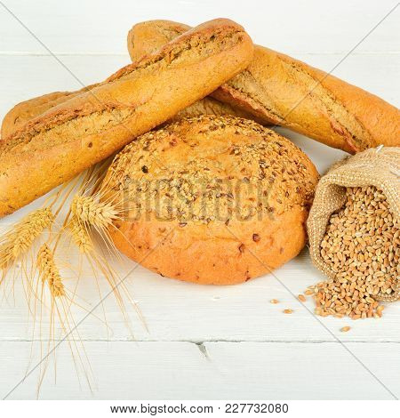Fresh Bread And Wheat On The Wooden Table. Healthy Food.
