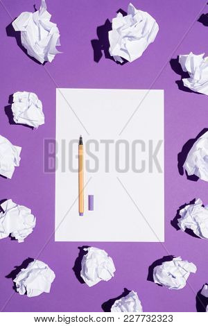 White sheet of paper and a pen laying on a vivid violet background with balls of paper. Blank page.
