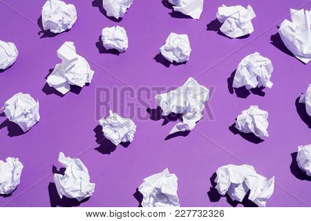 White balls of creased paper laying on a bright violet background. Recycling concept.