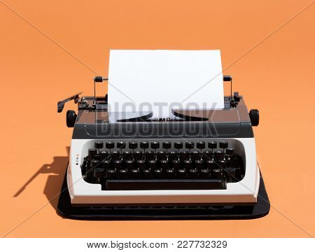 Oldschool typewriter with a blank page on an orange background. Writer concept.