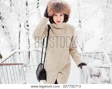 Adorable Happy Young Brunette Woman In Fur Hat Having Fun Snowy Winter Park Forest In Nature