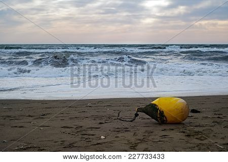 Yellow Buoy On The Beach After Storm
