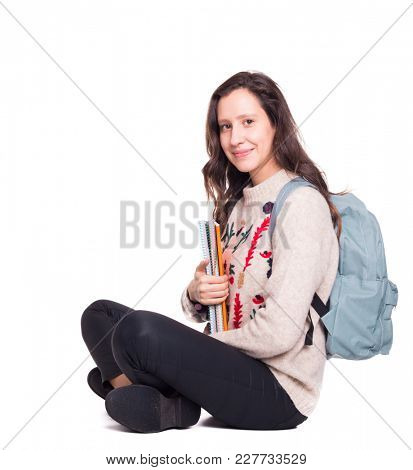 Student girl sitting on the floor with legs crossed with notebooks and backpack, isolated on a white background