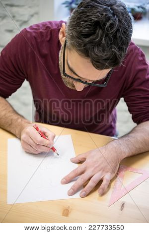 Young Designer Drawing the Sketch Using Pencil on the Wooden Table in the Bright Studio