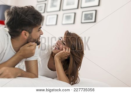 Young Couple In Love Lying In Bed After Waking Up, Cuddling