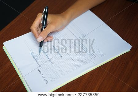 Close-up Of Hand Of Female Manager Filling In Or Reading Application Form On Table. Employment Conce
