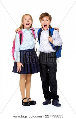 School fashion. Two cheerful children in school uniform and with school backpacks posing at studio. Isolated over white background. Copy space. Full length portrait.