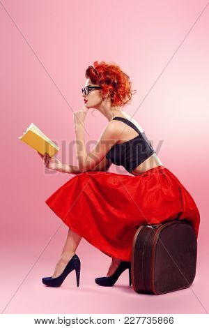 A pretty charming girl sits on a suitcase and reads a book on a pink background. Tourist trip concept. Copy space.