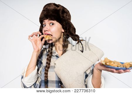 Funny Russian Girl In A Warm Hat With Earflaps Celebrates Shrovetide And Eagerly Eats Hot Pancakes