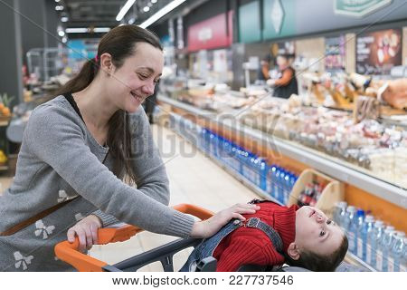 A Young Woman With A Small Son In A Supermarket. The Boy Sits In A Baby Cart And Laughs.