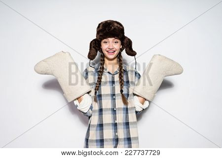 Smiling Young Girl From Russia In A Warm Fur Hat Holds Gray Felt Boots