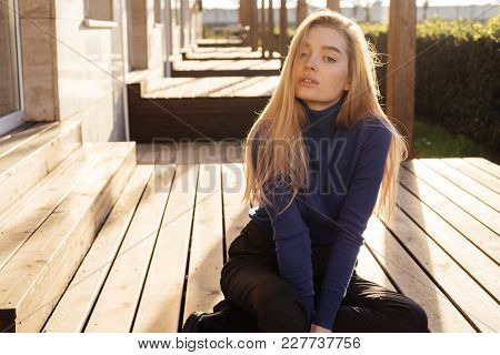 Cute Young Blonde Girl In Stylish Blue Sweater Sitting Outdoors In The Sun