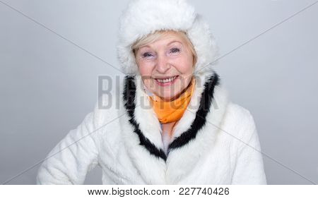 Adult Smiling Woman Is 70 Years Old. An Old Woman In A Light Fur Hat And Fur Coat Against A Light Ba