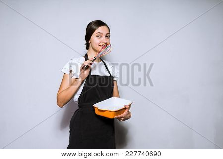 Beautiful Young Woman Cook In A Black Apron Preparing A Delicious Cake