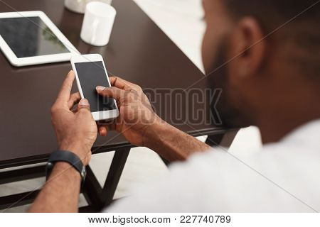 Closeup Of Male Hands Using Smartphone With Blank Screen At Home, Over Shoulder Shot, Copy Space
