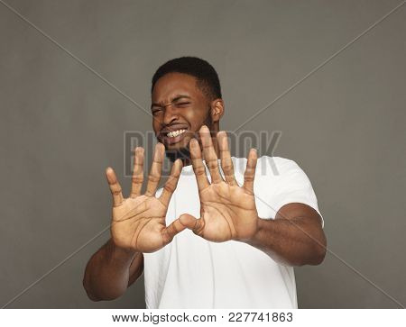 Black Man Expressing Disgust On Face, Grimacing On Grey Studio Background. Negative Emotions