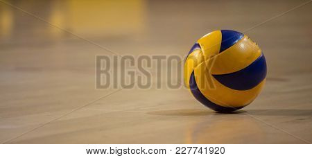 Volleyball ball, blue-yellow, with reflection. Blurred wooden parquetry background. Banner, space for text, close up view with details.