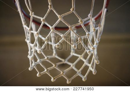 Basketball hoop, white net with knots. The target is the basket ring. Blurred background, close up view with details.